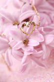 Gold necklace with heart on hyacinth Royalty Free Stock Photos