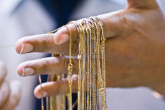 Gold necklaces 2. Hand holding 22k gold necklaces Royalty Free Stock Images