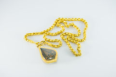 Gold necklaces and amulets. On white background Royalty Free Stock Photography