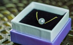 Gold neckless with white pearl. In white-purple box Stock Photo