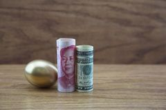 Gold nest egg with Chinese and American currency against wood ba Royalty Free Stock Image