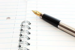 A gold nibbed pen on a notepad Royalty Free Stock Photo
