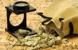 Gold Nugget. Loupe and Gold Nuggets royalty free stock photography