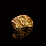 Gold nugget on black background. Royalty Free Stock Image