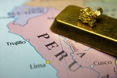 Gold nugget and gold bar and map of Peru. Close-up of a gold nugget and gold bar on top of a map of Peru royalty free stock photos