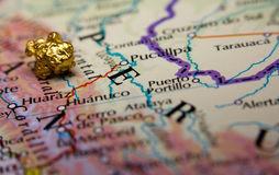 Gold nugget and map of Peru. Close-up of a gold nugget on top of a map of Peru stock photo