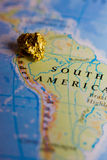 Gold nugget and map of Peru. Close-up of a gold nugget on top of a map of Peru stock photography