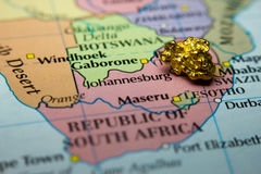 Gold nugget and map of South Africa. Close-up of a gold nugget on top of an old map of South Africa Stock Photo