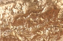 Gold nugget surface with broan stains. stock photography