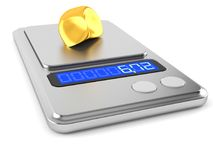 Gold nugget on weight scale. Isolated on white background Stock Photo