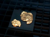 Gold nuggets. Two gold nuggets on black background royalty free stock image