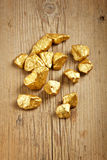 Gold nuggets. Raw gold nuggets on wood surface stock image