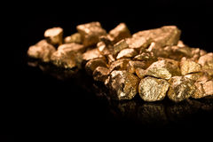 Gold nuggets on black background. Royalty Free Stock Images
