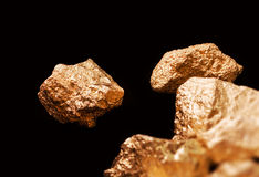 Gold nuggets on black background. Stock Photos