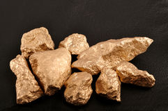Gold nuggets on a black background leather. Closeup. Gold nuggets on a black background leather Stock Photos