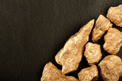 Gold nuggets on a black background leather. Closeup. Gold nuggets on a black background leather Stock Photo