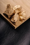 Gold nuggets on a black background leather and wood. Closeup. Royalty Free Stock Images