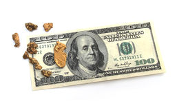 Gold nuggets and hudred dollar bill Royalty Free Stock Images