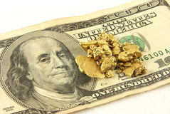 Gold Nuggets And Hundred Dollar Bill. Gold nuggets palced on top of a hundred dollar bill with a white background Stock Photos