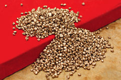Gold nuggets on red surface Royalty Free Stock Image
