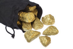 Gold nuggets scattered stones in a bag. Stock Photos