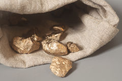 Gold nuggets spilling out from pouch on gray Royalty Free Stock Photo