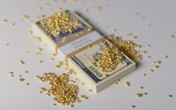 Gold and Money. Gold Nuggets on a Stack of US Dollar Notes royalty free stock photo
