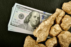 Gold nuggets and U.S. dollars on a black background leather. Clo. Seup Stock Photos