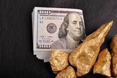Gold nuggets and U.S. dollars on a black background leather. Clo Royalty Free Stock Images