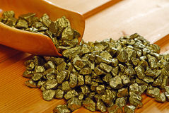 Gold nuggets and  wooden  scoop Royalty Free Stock Photography