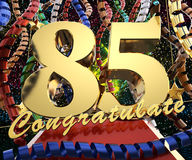 Gold number eighty five with the word congratulate on a background of colorful ribbons and salute. 3D illustration.  Royalty Free Stock Photography