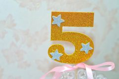 Gold number 5 five. Gold number 5 celebration candle against blurred light background Royalty Free Stock Image
