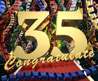 Gold number thirty five with the word congratulate on a background of colorful ribbons and salute. 3D illustration.  Stock Photo