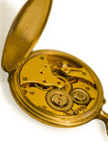 Gold old  clockwork. Isolated gold clockwork with shadow. Reverse side of a pocket watch. Cover is open. The mechanism is visible. Old invention Stock Photos