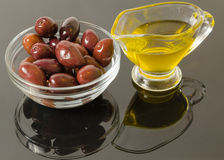 Gold olive oil with brown olives Stock Photos