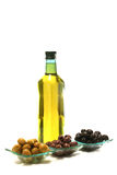 Gold olive oil in buttle with olives over white Royalty Free Stock Photos