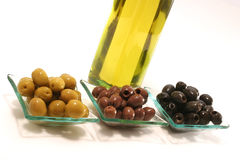 Gold olive oil in buttle with olives over white Royalty Free Stock Image