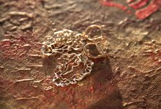 Gold openwork earrings on a picturesque terracotta background. Gold earrings lying on the picture painted in oil in Buddhist style stock image
