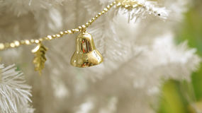 Gold ornament on white Christmas tree. With copy space Stock Photo