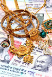 Gold ornaments on Indian currency Stock Photography