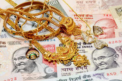 Gold ornaments on Indian currency Royalty Free Stock Image