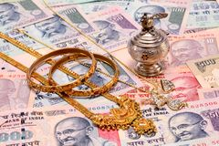 Gold ornaments on Indian currency Stock Images