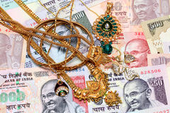 Gold ornaments and Indian currency Royalty Free Stock Image