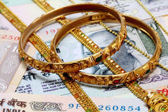 Gold ornaments on Indian currrency Royalty Free Stock Images