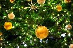 Gold Ornaments on Tree. Many Gold and Silver Ornaments with Lights on a Green Christmas Tree stock photo