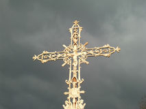 Gold ornate cross on dark sky. Golden ornate cross against dark, cloudy sky Royalty Free Stock Photo