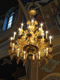 Gold ornated luxurious luster in interior of church Stock Images