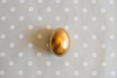 Gold-Osterei auf punktiertem Hintergrund Lizenzfreie Stockfotos