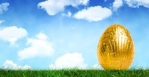 Gold-Osterei vor blauem Himmel Stockbilder