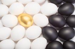 Gold-Osterei zwischen vielen weißen und schwarzen Eiern Stockbild